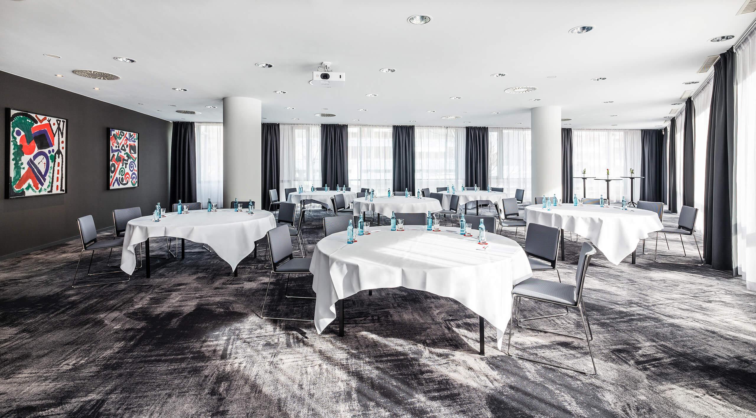 Tagungsraum mit runden Tischen in Kabarett Bestuhlung, mit Tageslicht und Klimaanlage